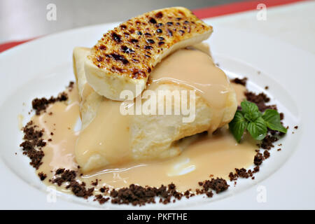 Sweet pancake - crepe in caramel sauce with muscovado dark brown sugar and caramelized banana, mint leaf - Stock Photo