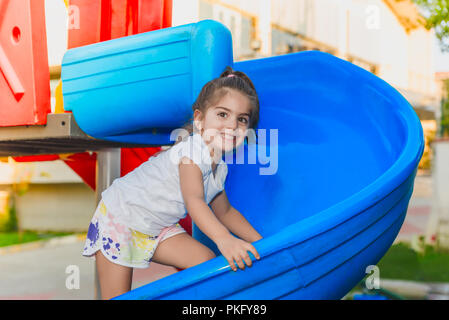 Portrait of cute little girl holding and climbing sliders to reach top  on playground - Stock Photo