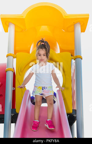 Portrait of cute little girl trying to walk on pink slider from top to bottom on playground - Stock Photo
