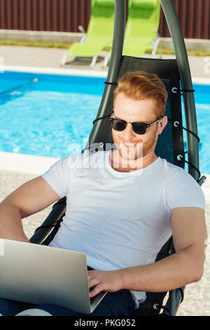 handsome young man sitting in sun lounger in front of swimming pool and working with laptop - Stock Photo