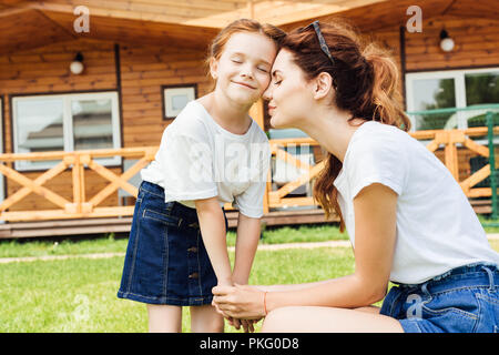 beautiful mother and daughter cuddling and holding hands in front of wooden cottage - Stock Photo