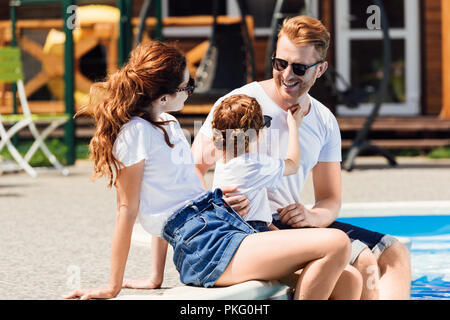 smiling young family in white t-shirts and sunglasses sitting on poolside together - Stock Photo