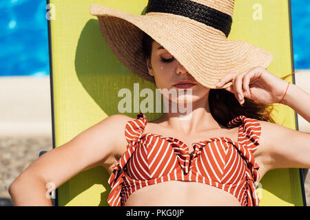 close-up portrait of attractive young woman in straw hat and bikini relaxing on sun lounger at poolside - Stock Photo