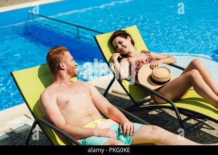 happy young couple flirting while relaxing on sun loungers in front of swimming pool - Stock Photo