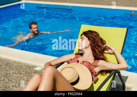 young woman relaxing on sun lounger while her boyfriend swimming in pool on background - Stock Photo