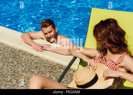 young man flirting with woman lying on sun lounger while swimming in pool - Stock Photo
