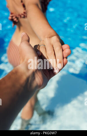 cropped shot of man holding hand of wife in swimming pool, follow me concept - Stock Photo
