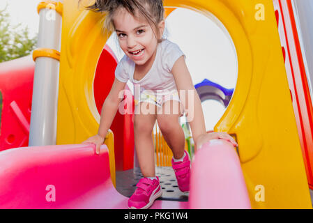 Portrait of cute little girl holding  and sliding on sliders on playground - Stock Photo