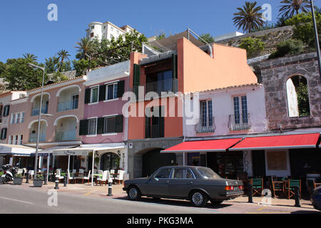 Spain. Balearic Islands. Menorca. Mahón. Harbourside buildings with restaurants and cafés with parked classic Mercedes car. - Stock Photo