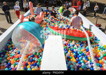 Southbank, London, UK, 13th Sep 2018. People have fun with 'Say Balls To Boring'in the London sunshine. Claimed to be the UK's biggest outdoor ball pit, it opens on the Southbank in London today. The pit contains 140,000 colourful balls for a 'kidult lido' in which visitors can take a dip. Credit: Imageplotter News and Sports/Alamy Live News - Stock Photo