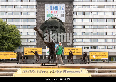 Chemnitz, Germany - September 13, 2018: A passer-by takes a look at a brass wolf saluting Heil Hitler with the National Socialists' greeting. The installation by the artist Rainer Opolka, which was set up today, is intended to counter a sign against hatred and violence after the great right-wing demonstrations a good two weeks after the murder of a German in Chemnitz by refugees. Credit: Mattis Kaminer/Alamy Live News - Stock Photo