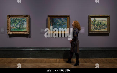 National Gallery, London, UK. 13 September, 2018. An exhibition bringing together the Impressionist and Post-Impressionist collections of the Courtauld Gallery and National Gallery with many iconic works of art on display, the exhibition runs from 17 September 2018 - 20 January 2019. Photo: Paul Cézanne, landscapes. Left: Tall Trees at the Jas de Bouffan, about 1883; Centre: Lac d'Annecy, 1896; Right: Farm in Normandy, Summer (Hattenville), about 1882. The Courtauld Gallery, London. Posed with gallery staff. Credit: Malcolm Park/Alamy Live News. - Stock Photo