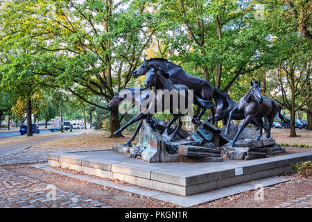 Berlin,Dahlem. Bronze sculpture of five wild horses jumping over remains of Berlin Wall. Gift from USA to FDR commemorates the day the wall fell - Stock Photo