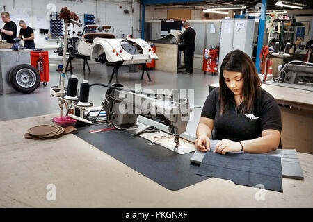 female machinist making leather seat squabs at Morgan Cars Malvern England UK - Stock Photo