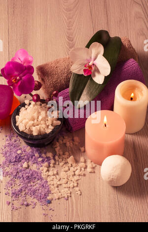Spa setting with orchid flowers, bowl with sea salt, candles, soap and towels on wooden board - Stock Photo