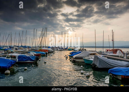 Small boats sheeted and moored along a pontoon on the lake Geneva under a stormy sky, Haute Savoie department, Auvergne Rhone Alpes, France - Stock Photo