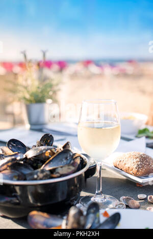 Mussels in a saucepan and a glass of cold white wine. Delicious seafood dinner in a restaurant on the beach. Copy space.