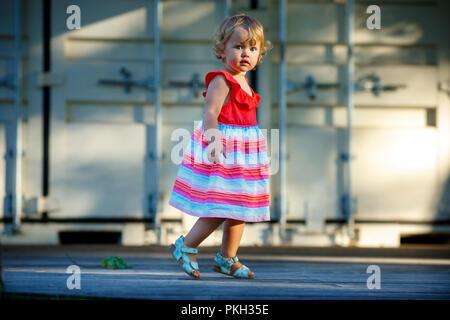 Sweet blond little baby girl in beautiful dress plays walks outdoors - Stock Photo