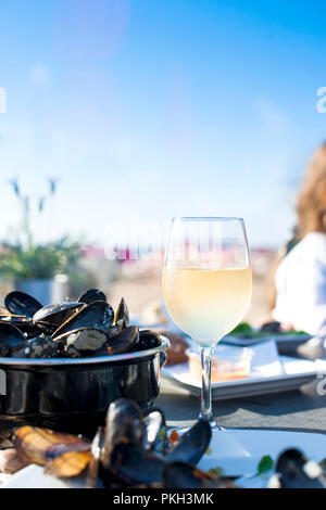 Mussels in a saucepan and a glass of cold white wine. Delicious seafood dinner in a restaurant on the beach. Copy space
