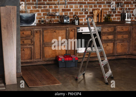 interior of loft style kitchen with stepladder, toolbox and laminate planks on floor - Stock Photo