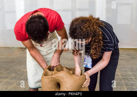 Two young Caucasian students working on a sculpture in an atelier - Stock Photo