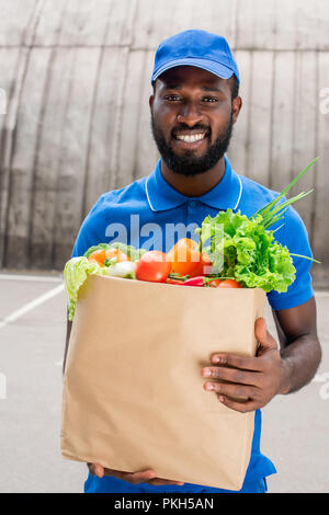 smiling african american delivery man holding paper bag with vegetables - Stock Photo