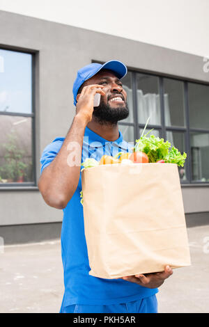 african american delivery man holding paper bag with vegetables and talking by smartphone - Stock Photo