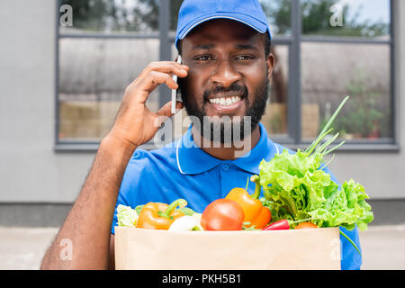 smiling african american delivery man holding paper bag with vegetables and talking by smartphone - Stock Photo