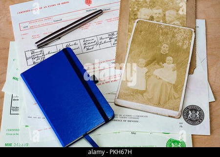 Collection of birth, marriage, death certificates & a notebook with some old photographs used for family history research, England, UK - Stock Photo