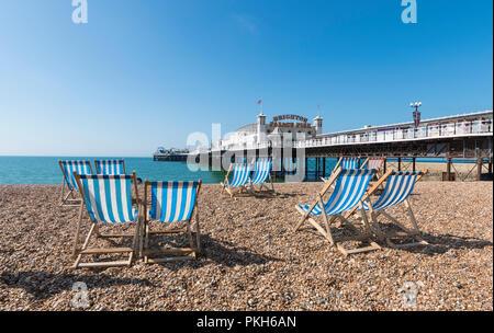 Brighton Palace Pier, empty deckchairs and beach in Summer in Brighton beach, Brighton, East Sussex, England, UK. - Stock Photo