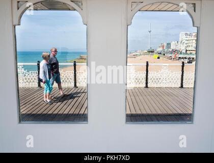 brighton piers wooden boardwalk with coastline and brighton eye in background - Stock Photo