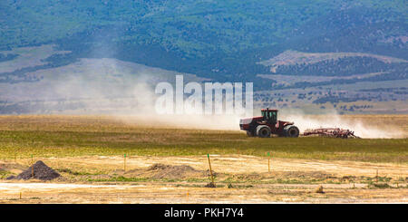Red tractor with large wheels on a field in Utah - Stock Photo