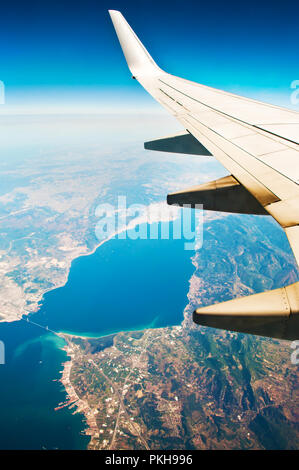 White airplane wing. Blue sea surface, ragged coast, sky, horizon. Aerial view of suspension bridge across Gulf of Izmit, long winding road, colorful  - Stock Photo