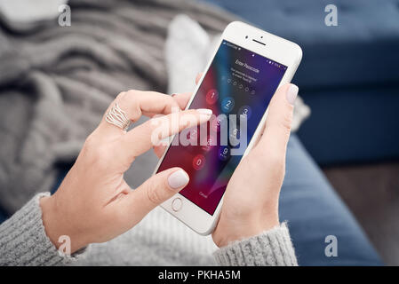 Kyiv, Ukraine - January 24, 2018: Woman holding a brand new Apple iPhone 8 plus and enter passcode.The cellular phone is produced by Apple Computer, I - Stock Photo