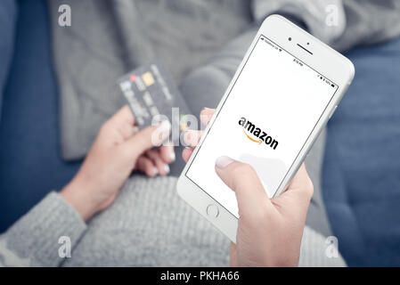 Kyiv, Ukraine - January 24, 2018: Woman holding Apple Iphone 8 plus with loading Amazon mobile app at home closeup. - Stock Photo