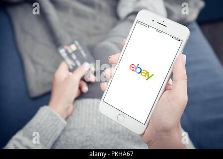 Kyiv, Ukraine - January 24, 2018: Woman holding Apple Iphone 8 plus with loading Ebay mobile app at home closeup. - Stock Photo