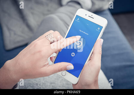 Kyiv, Ukraine - January 24, 2018:  Woman hands using Shazam application on Apple Iphone 8 plus for searching music what she like while lying at home o - Stock Photo