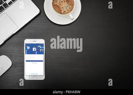 Kyiv, Ukraine - Fabruary 6, 2018: Apple iPhone 8 plus with Facebook app on the screen on black desk with MacBook and coffee, top view.Facebook is a so - Stock Photo