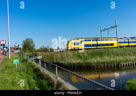 Netherlands,Lisse,Europe, a train crossing a bridge over a body of water - Stock Photo