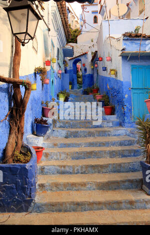 Typical street, beautifully decorated with pots from the touristic Moroccan village of Chefchaouen - Stock Photo