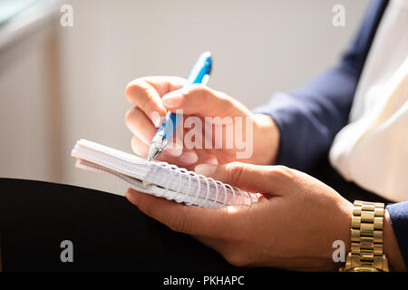 Close-up Of A Businesswoman's Hand Writing Note With Pen In Spiral Notepad - Stock Photo