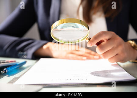 Close-up Of A Businesswoman's Hand Looking At Contract Form Through Magnifying Glass - Stock Photo