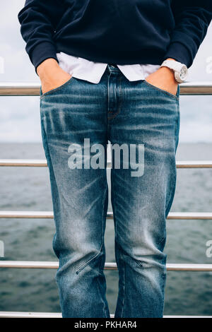 Details of casual clothing in blue and white colors. Lifestyle close-up of fashionable female wearing wristwatches holding hands in pockets of jeans s - Stock Photo