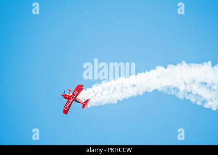 Oshkosh, WI - 28 July 2018:  A bi-plane sponsored by Oracle does stunts at an airshow - Stock Photo