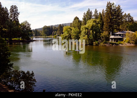 Two paddleboarders enjoy a summer afternoon on the Deschutes River in downtown Bend, Oregon - Stock Photo
