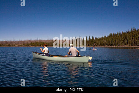 A middle aged married couple paddling a canoe on Waldo Lake, a volcanic caldera lake in the central Oregon Cascades near the town of Oakridge. - Stock Photo