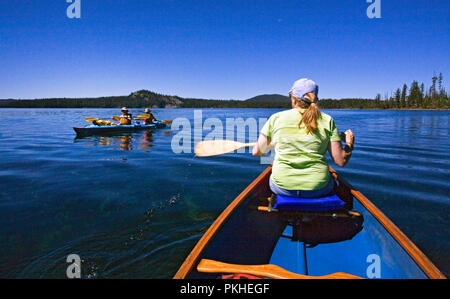 A middle aged married couple paddling a two-person kayak on Waldo Lake, a volcanic caldera lake in the central Oregon Cascades near the town of Oakrid - Stock Photo