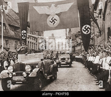 Adolf Hitler, on a victory drive, crossing the frontier from Germany into the Nazi Sudetenland districts of Czechoslovakia, October 3, 1938.   Adolf Hitler,1889 – 1945. German politician, demagogue, Pan-German revolutionary, leader of the Nazi Party, Chancellor of Germany, and Führer of Nazi Germany from 1934 to 1945.   From These Tremendous Years, published 1938. - Stock Photo