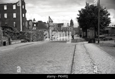 1950s, historical, view down an old cobbled street in the city of Cologne, Germany showing empty bombed out buildings remaining from the allied offensives during the second World War. - Stock Photo