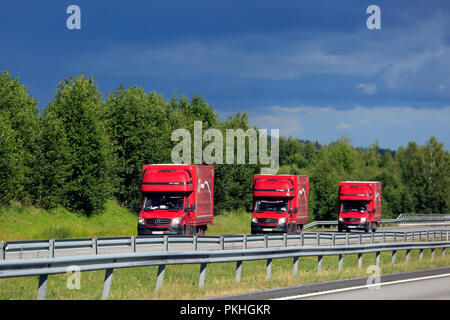 Three red Mercedes-Benz light trucks platoon on motorway on an overcast day of summer. Salo, Finland - July 6, 2018. - Stock Photo